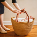 A newborn baby sleeping in a Moses basket. Lifestyle photo by Laura Mares Photography, Pittsburgh Newborn Photographer.