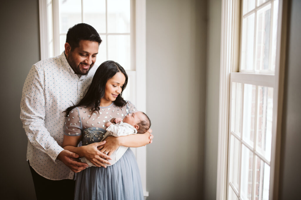 A couple holding their newborn baby. Lifestyle photo by Laura Mares Photography, Pittsburgh Newborn Photographer.