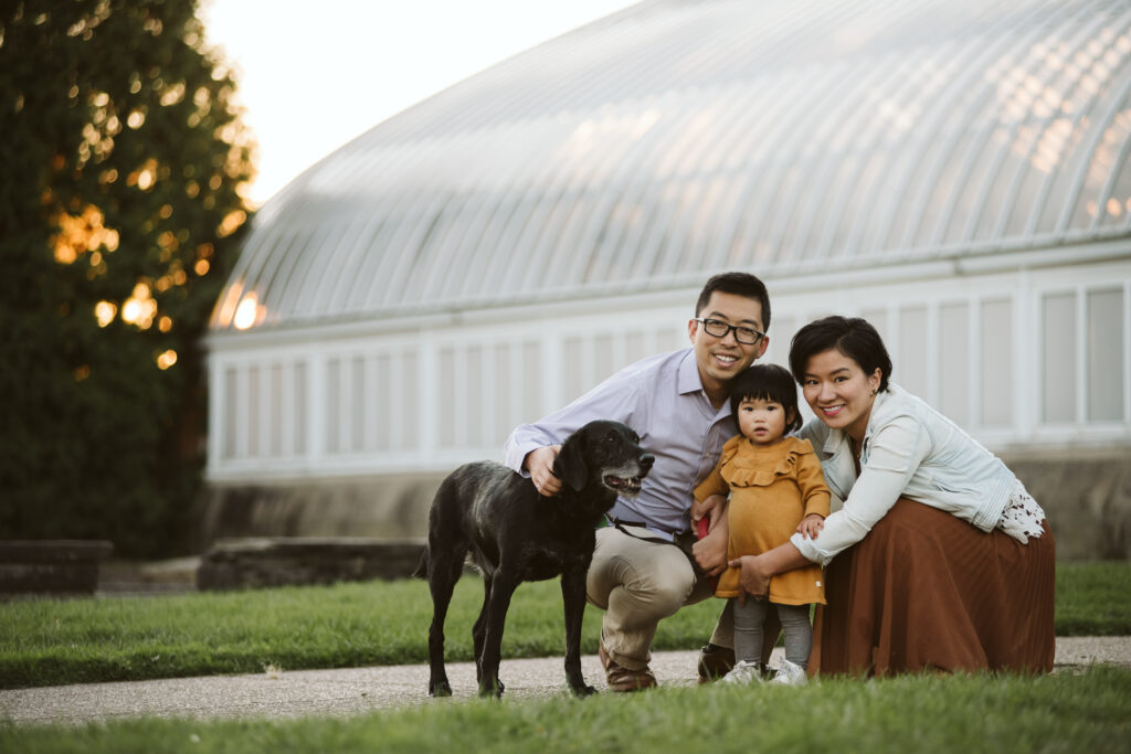 family of 3 at sunset with their black dog near Phipps Conservatory