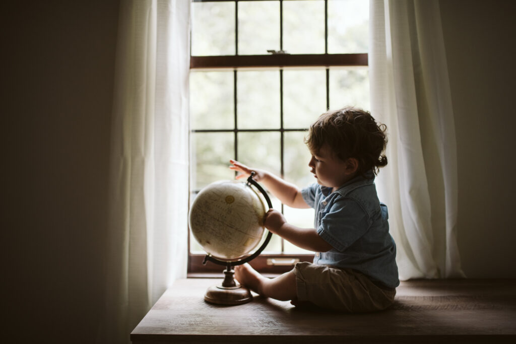 A toddler boy sitting inside a window lookin at a globe. Lifestyle photo by Laura Mares Photography, Pittsburgh Lifestyle Photographer.