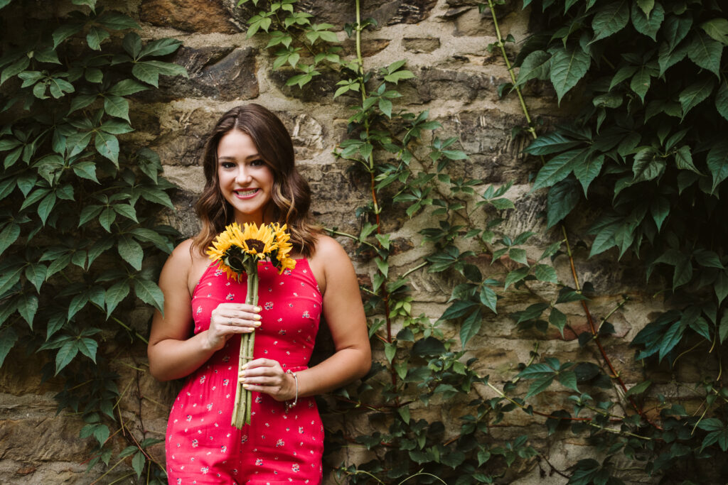 Portrait of a senior girl leaning against a brick wall holding a sunflower. Photo by Laura Mares Photography, Pittsburgh Senior Photographer