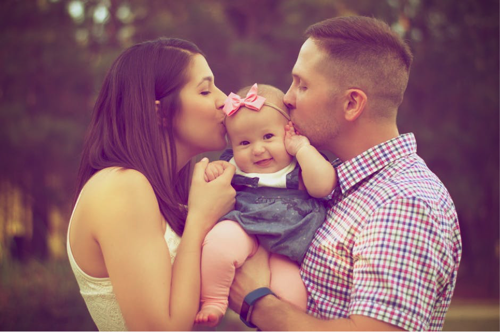 mother and father kissing their baby daughter