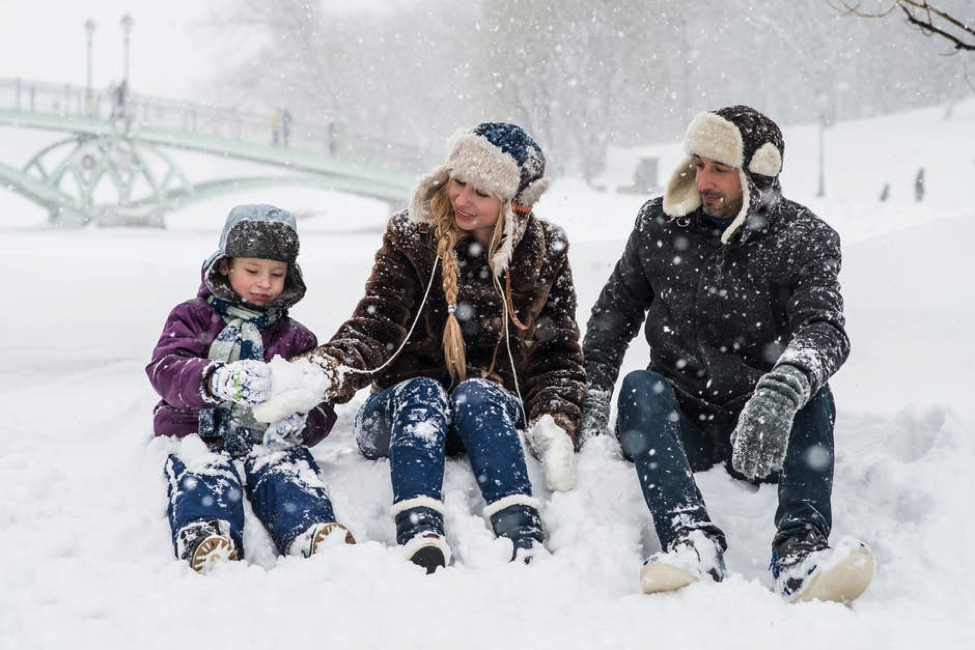 Family stilling together playing with snow.