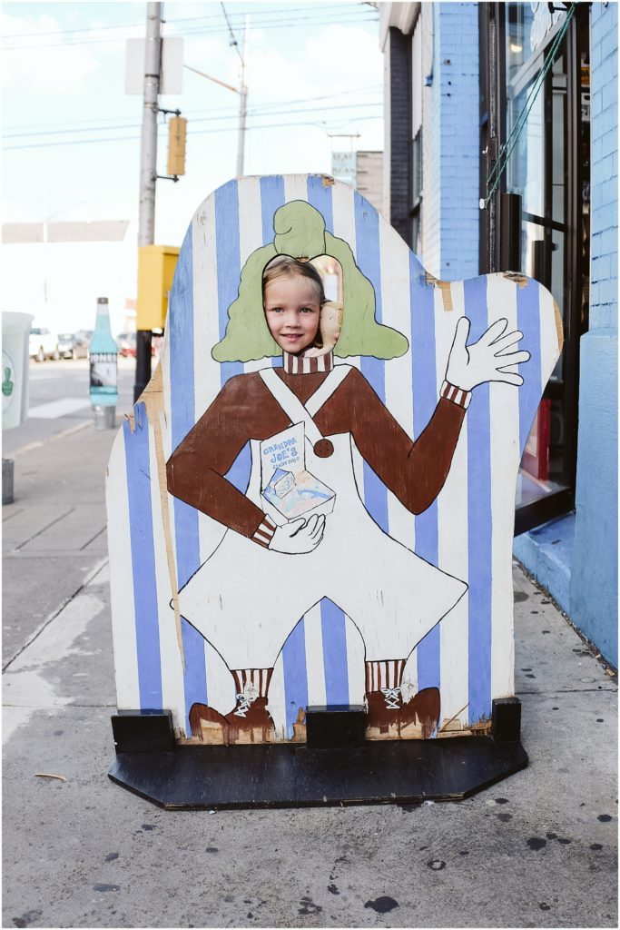 Girl standing infant of a grandpa Joe's sign. Photo by Laura Mares Photography, Pittsburgh Child Photographer.