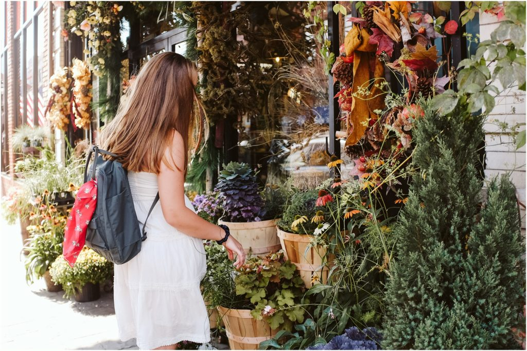 Girl sitting in front of a floral shop. Photo by Laura Mares Photography, Pittsburgh Senior Photographer.