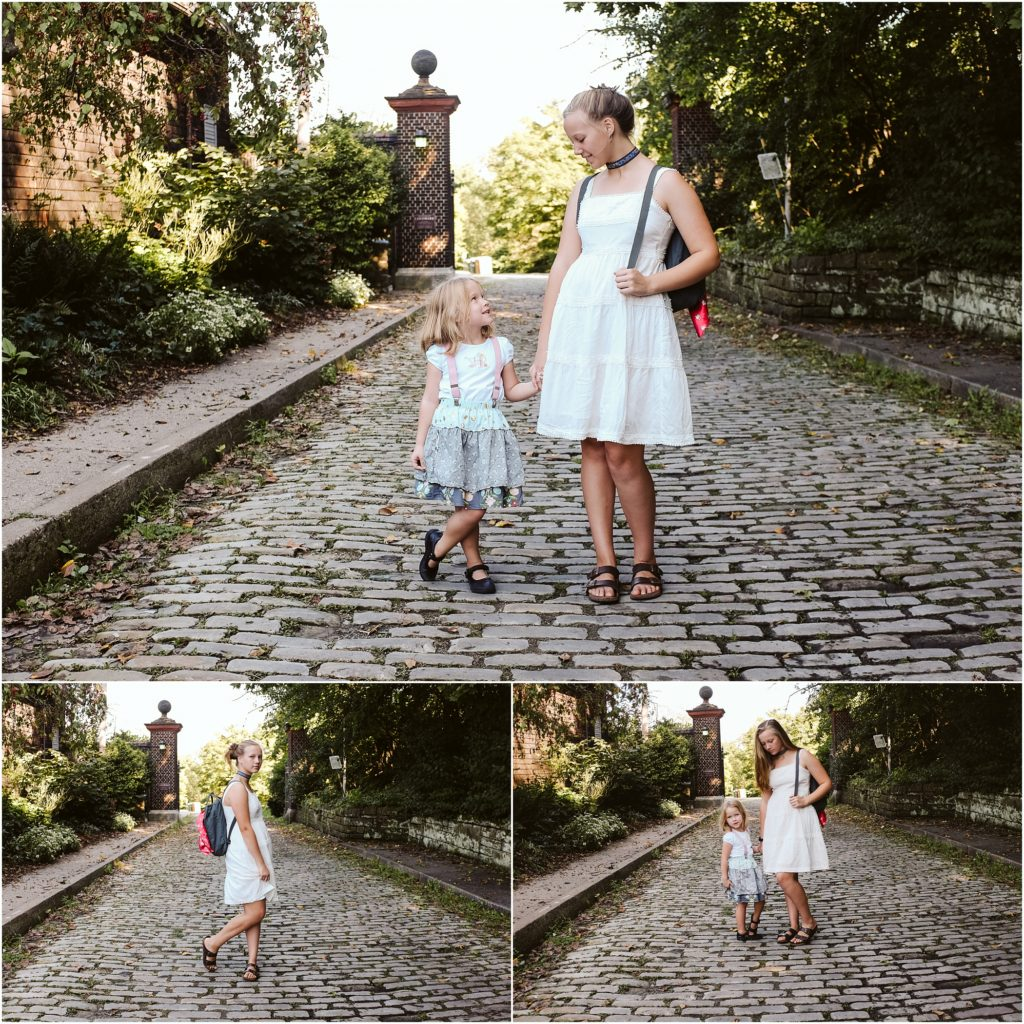 Sisters standing on a cobblestone road. Photo by Laura Mares Photography, Pittsburgh Lifestyle Photographer.
