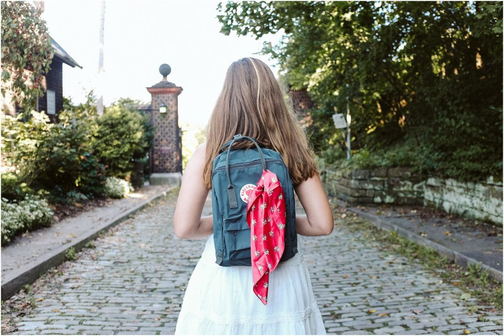 Girl standing on a cobblestone road wearing a fjallraven Kanken backpack. Photo by Laura Mares Photography, Pittsburgh Lifestyle Photographer.