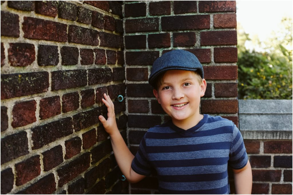Boy standing in front of a brick wall. Photo by Laura Mares Photography, Pittsburgh Child Photographer.