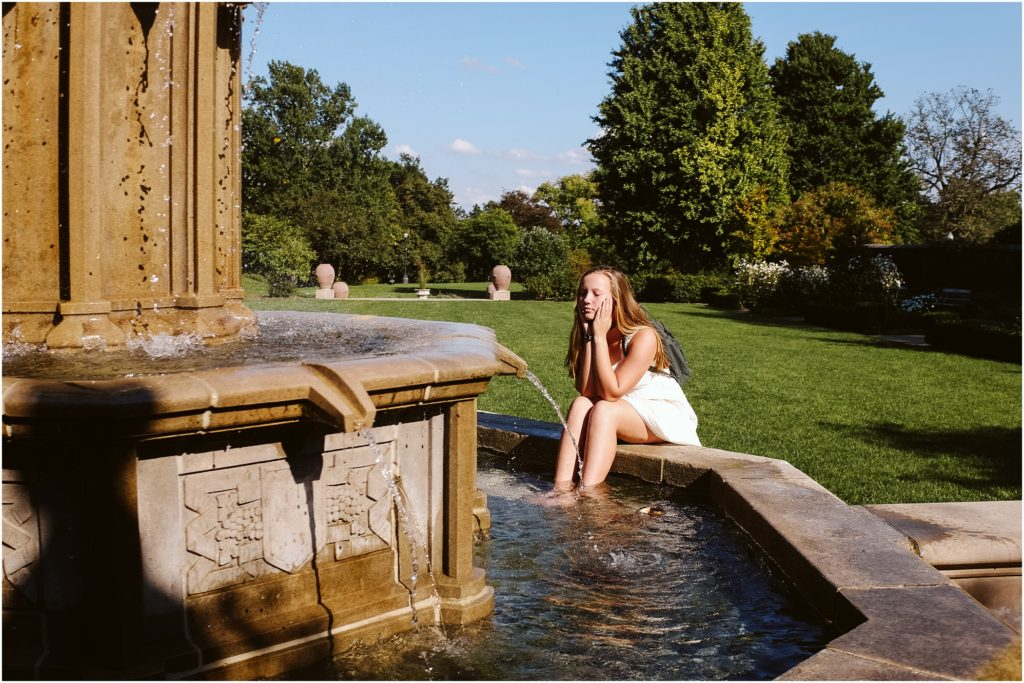 Girl sitting at a fountain in Mellon Park. Photo by Laura Mares Photography, Pittsburgh Senior Photographer.