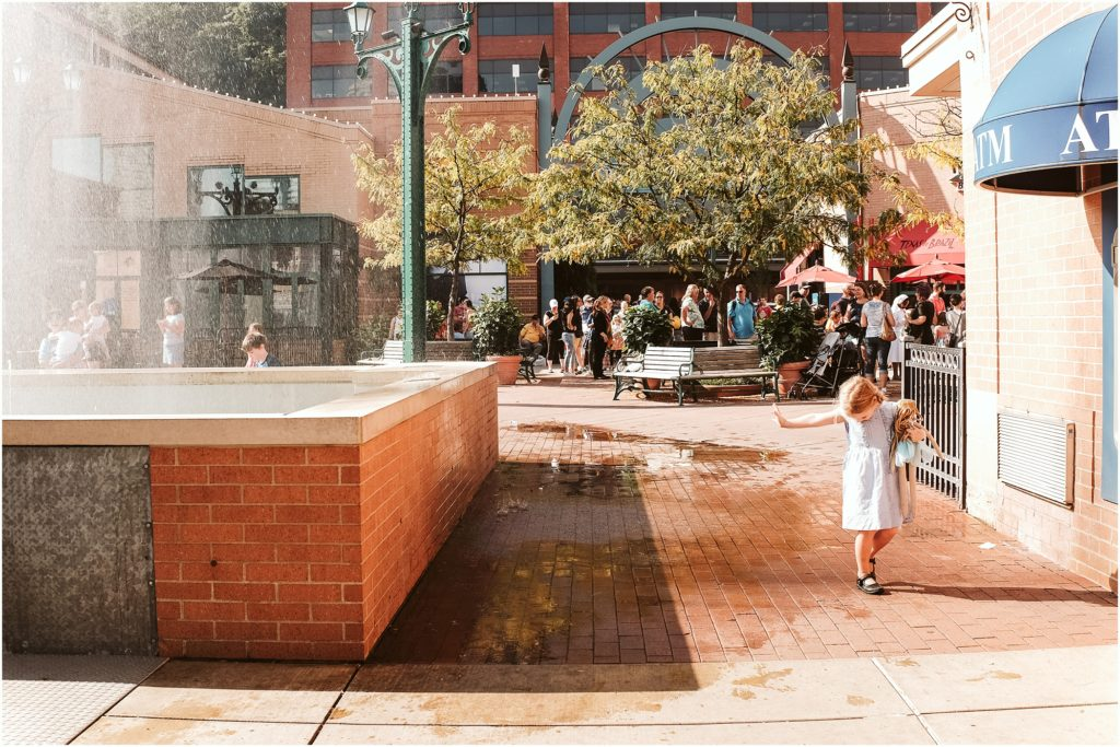 Girl walking near the fountain at Station Square. Photo by Laura Mares Photography, Pittsburgh Child Photographer.