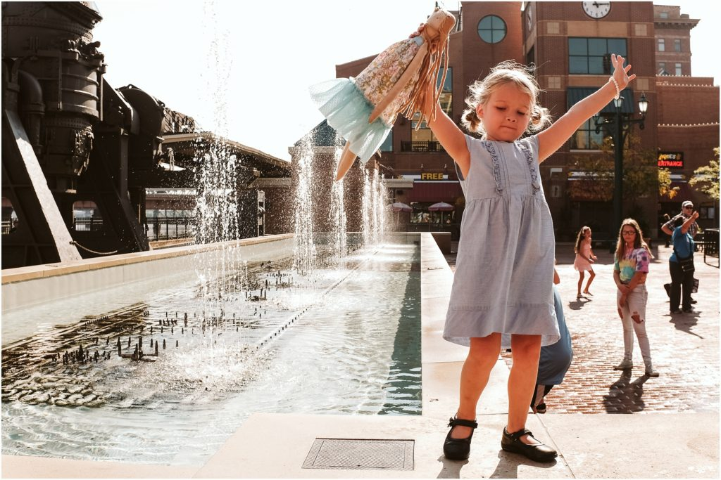 Girl standing on the fountain at Station Square. Photo by Laura Mares Photography, Pittsburgh Child Photographer.