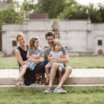 Family of four sitting on the step at Mellon Park