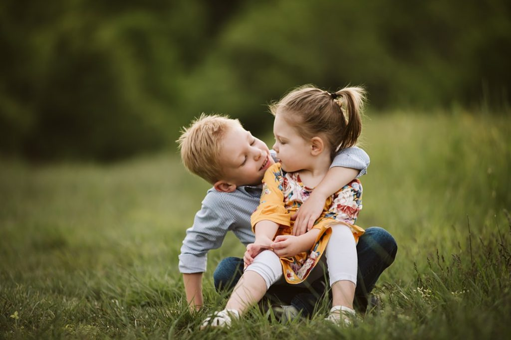 Portrait of two children whispering while sitting on a field. Photo by Laura Mares Photography, Pittsburgh Family Photographer.