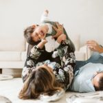 A lifestyle image of a family playing together to celebrate a birthday. Photo by Pittsburgh Newborn Lifestyle Photographer, Laura Mares Photography.
