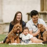 A portrait of a family of three with their two doodles sitting in a park near Pittsburgh. Portrait by Laura Mares Photography, Pittsburgh Family Photographer