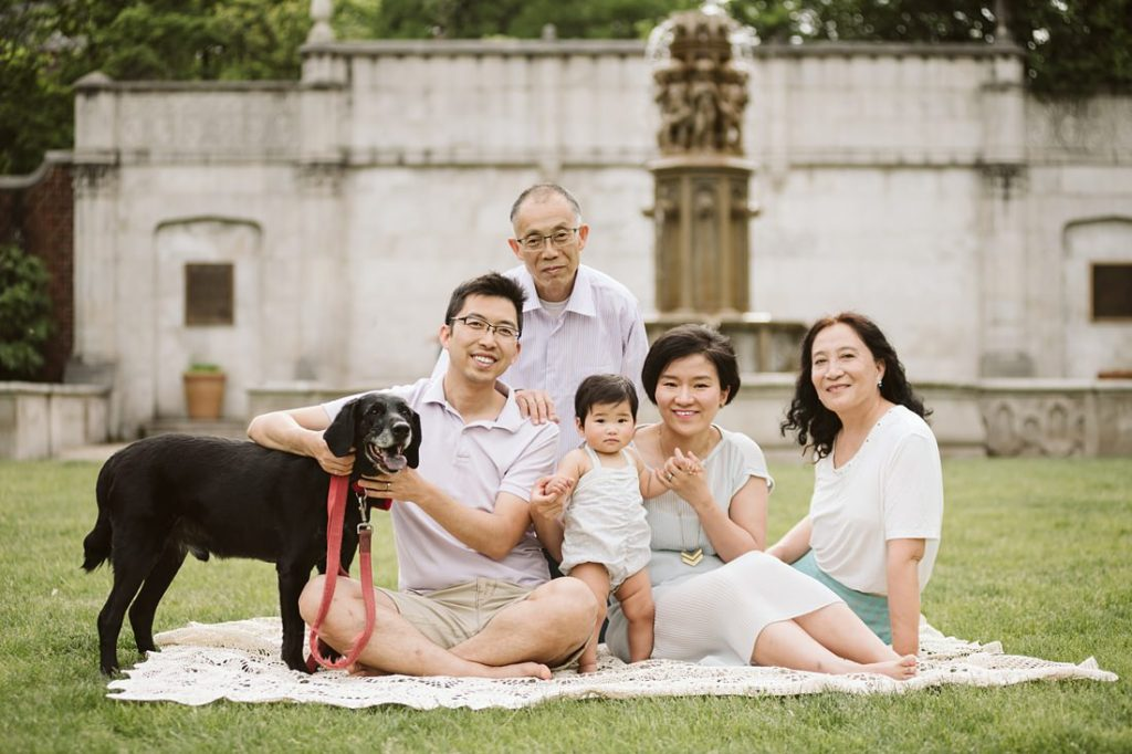 A portrait of a family sitting in a park with their dog near Pittsburgh. Portrait by Laura Mares Photography, Pittsburgh Family Photographer