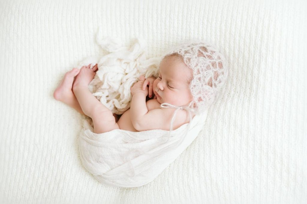 A portrait of a newborn baby girl wrapped in a white wrap near Pittsburgh. Portrait by Laura Mares Photography, Pittsburgh Newborn Photographer