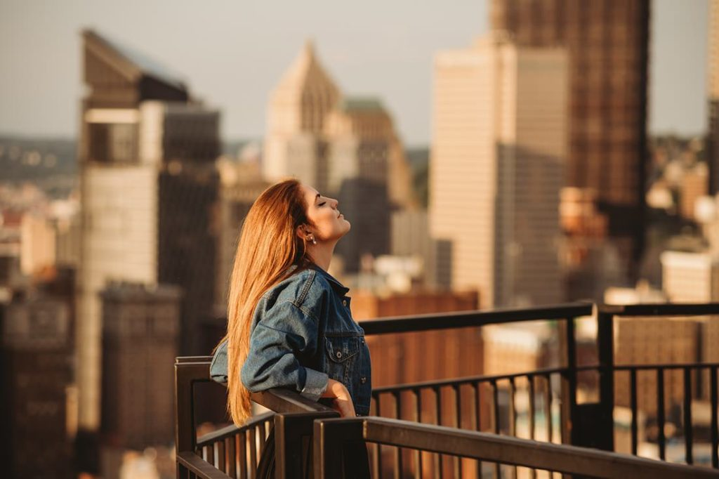 A portrait of a senior girl standing on Mt. Washington at sunset, Pittsburgh. Portrait by Laura Mares Photography, Pittsburgh Senior Photographer