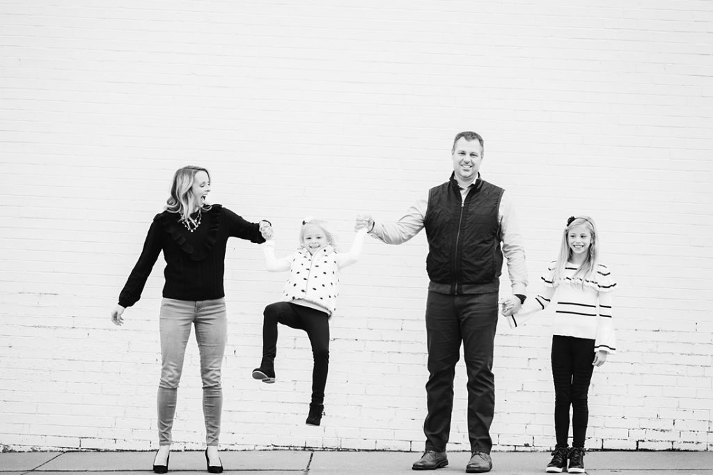 Black and white Urban Family Portrait with white brick wall. Portrait taken by Laura Mares Photography, Pittsburgh Family Photographer.