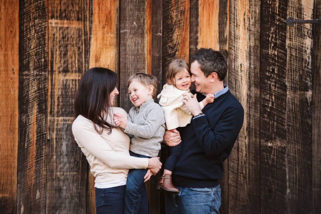 family of four hugging and laughing in front of a wooden background