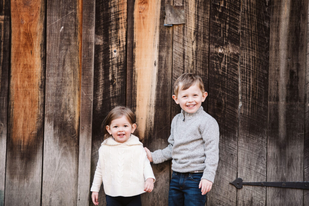 children holding hands in front of a wooden background