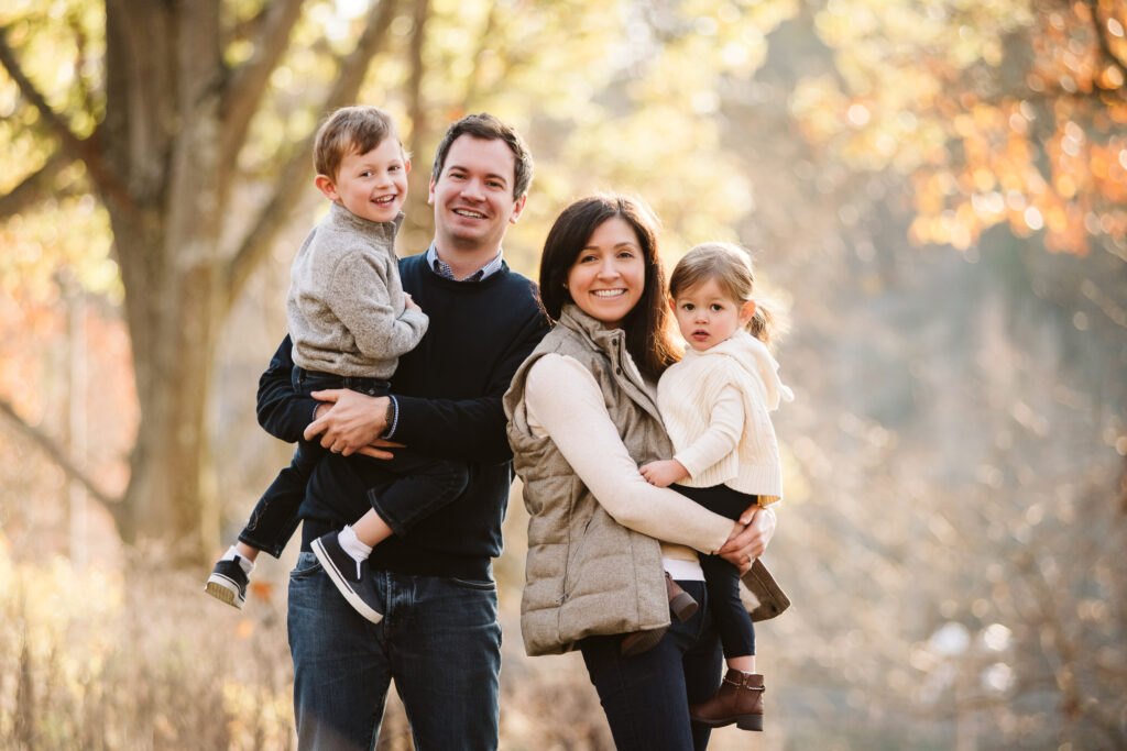 a family of four posing for a fall family photo