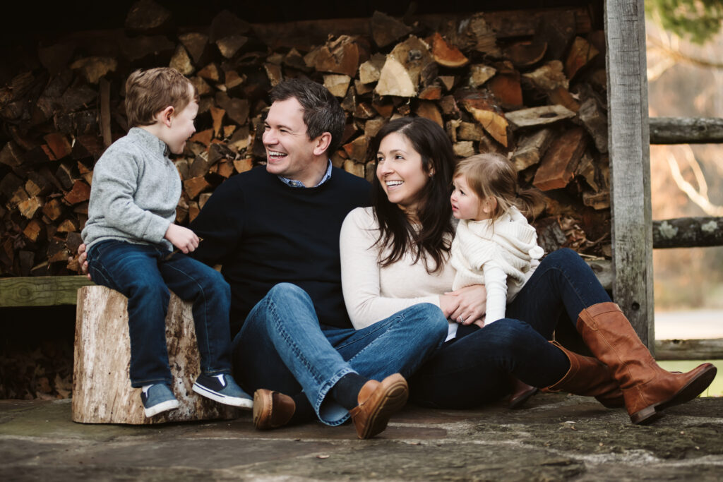 a family of four sitting together for a picture infront of a wood pile