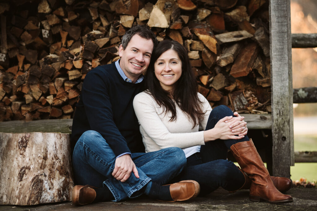 a couple sitting together for a picture infront of a wood pile
