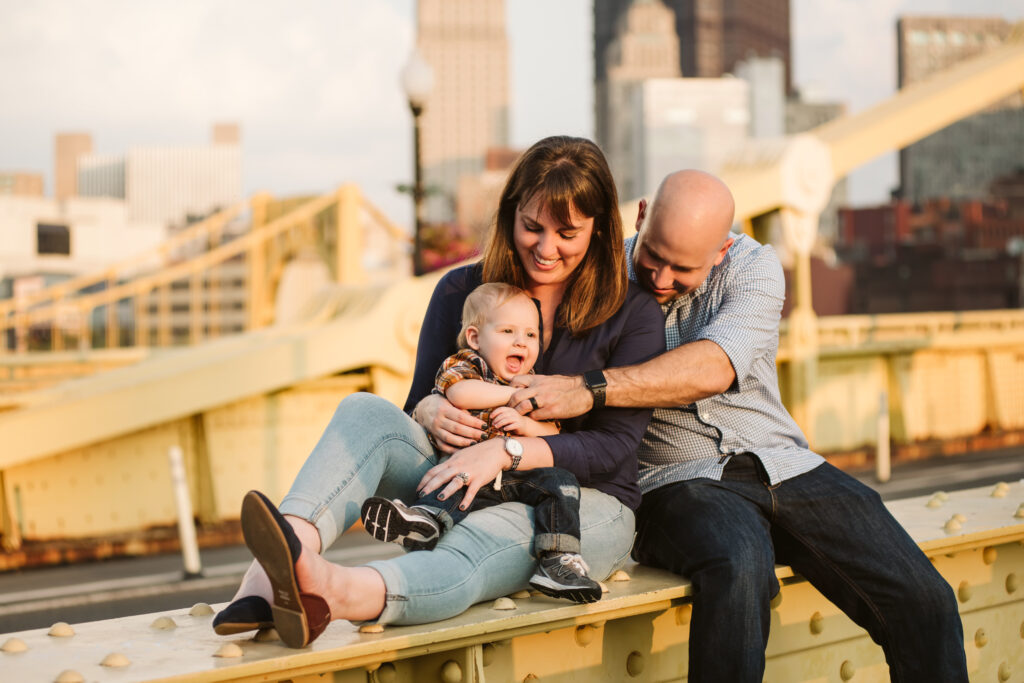 a family of three sitting on a yellow bridge at sunset
