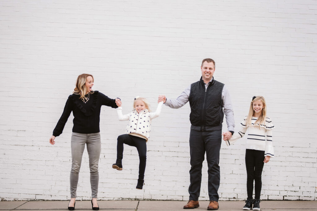 a family of four standing in front of a white brick wall
