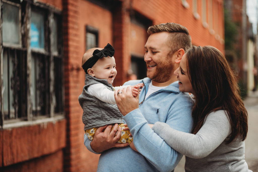a family of three looking at each other in front of a brick wall in North Side of Pittsburgh