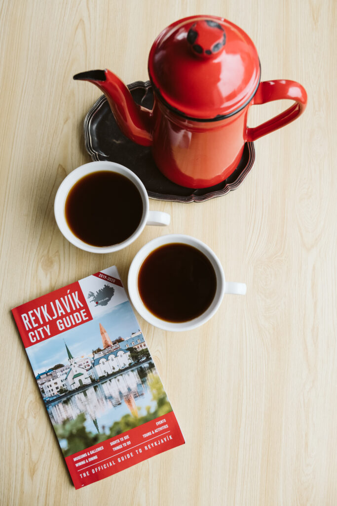 Red coffee pot, two cups of black coffee and a Reykjavik city guide.