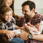 at home lifestyle photo of a family sitting on a sofa holding their newborn baby