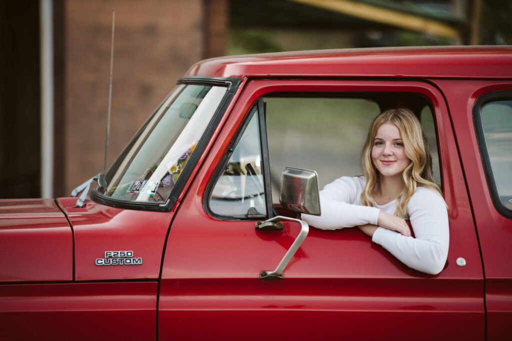 portrait of a senior girl sitting in a red ford truck near Pittsburgh, PA