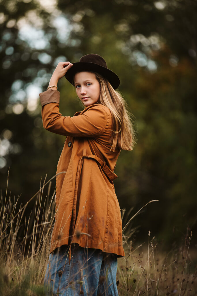 a high school senior girl wearing a trench coat and cowgirl hat standing in a beautiful field at sunset