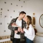 loving parents holding newborn in modern bohemian nursery