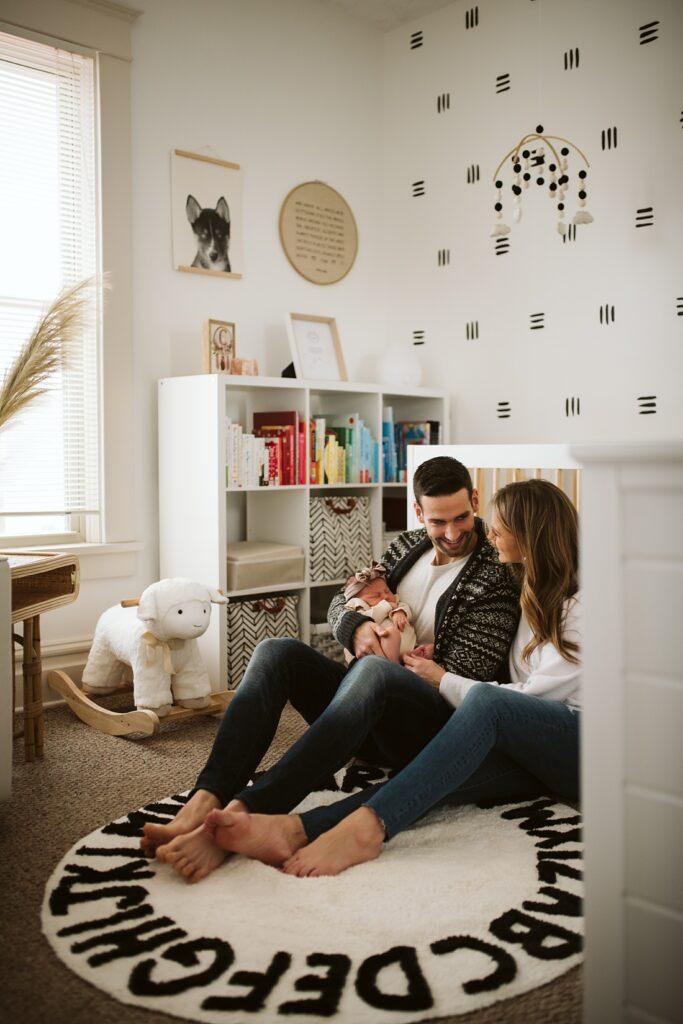 Parents sitting in a modern boho nursery holding newborn baby near Pittsburgh, PA
