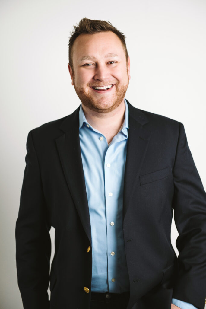 Professional headshot of a business man wearing a black suit with a white background. Portrait taken by Laura Mares Photography, Pittsburgh Photographer.