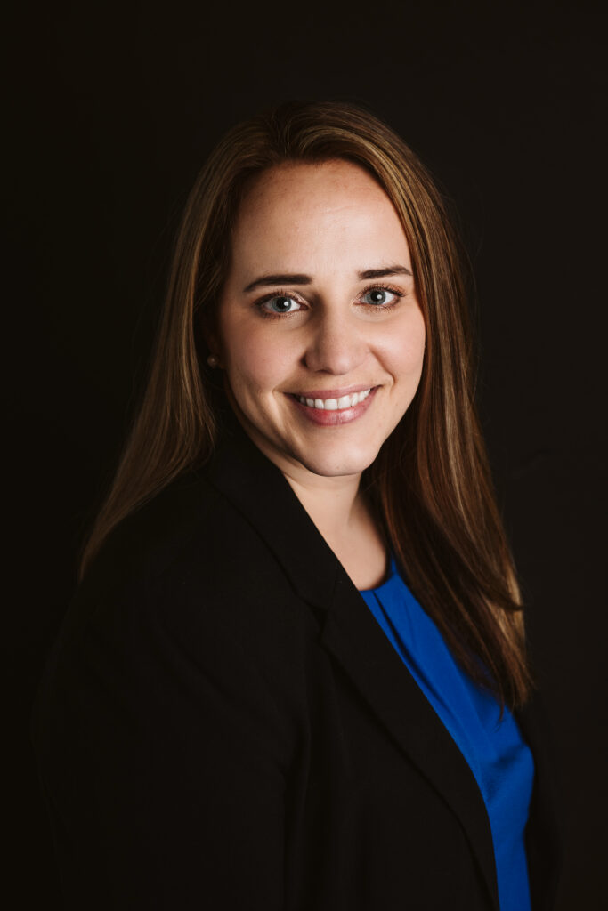 Professional headshot of a business woman wearing a black suit with a black background. Portrait taken by Laura Mares Photography, Pittsburgh Photographer.