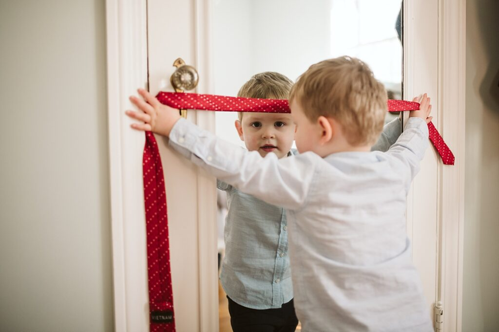 lifestyle photo of a boy holding his dad's tie while looking in the mirror