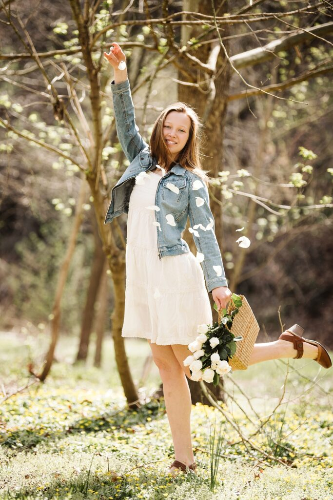 senior pictures of a girl dropping rose petals in a forest near Pittsburgh