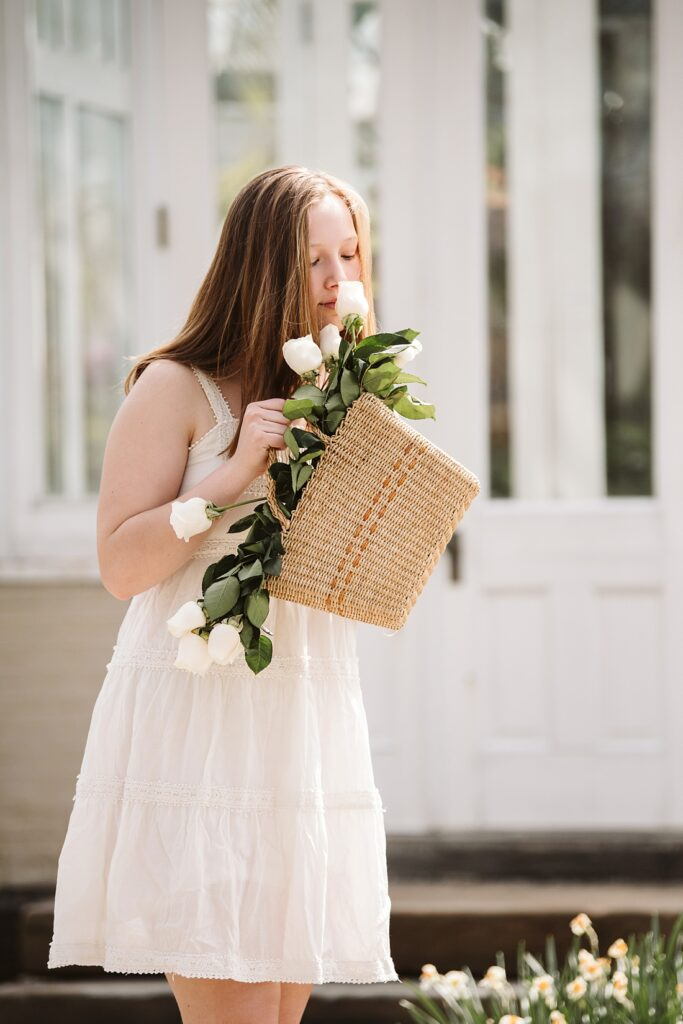 senior girl smells roses from a wicker basket near a greenhouse in Frick Park