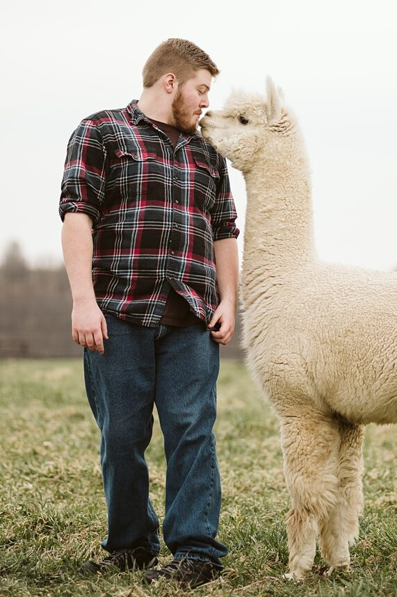 A portrait of a senior guy up close with an alpaca near Pittsburgh. Portrait by Laura Mares Photography, Pittsburgh Senior Photographer